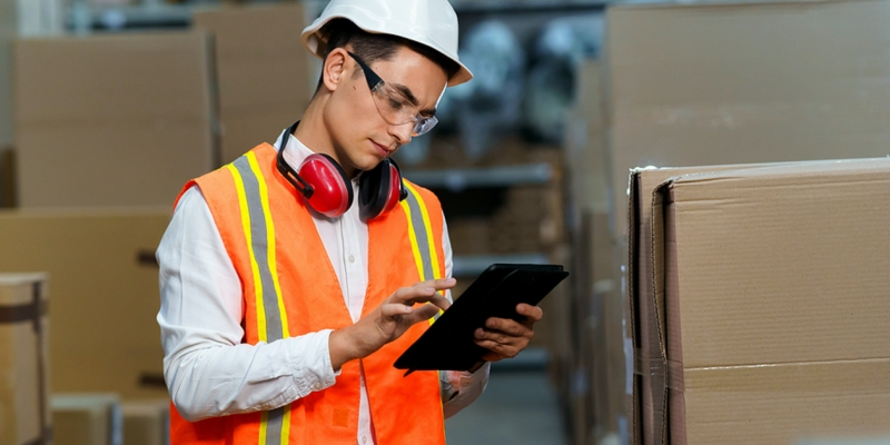 Worker with a hardhat and safety vest using a tablet.