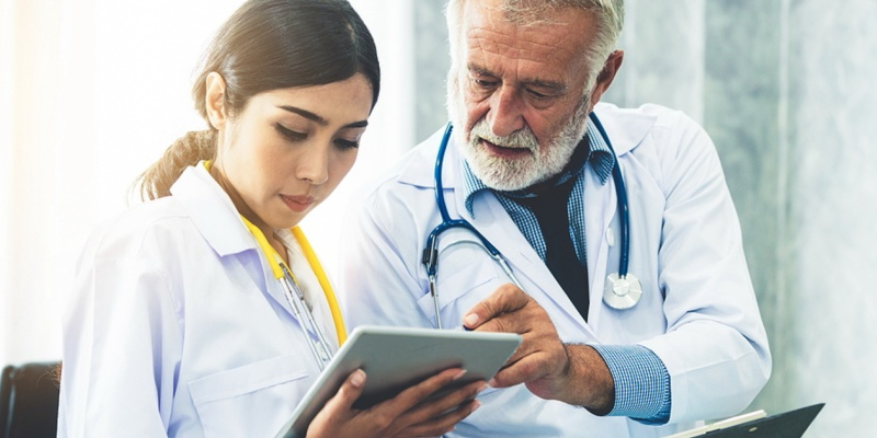 Two medical doctors discussing information on a tablet.