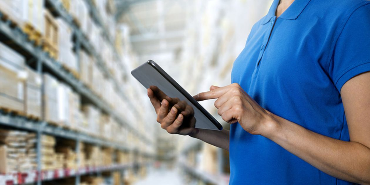 Typing on a tablet in a warehouse.